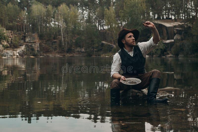 Le golddigger Unshaved lave l'or dans le lac avec la banque rocheuse photographie stock libre de droits