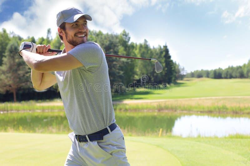 Le golfeur frappe un fairway tir? vers la maison de club image libre de droits