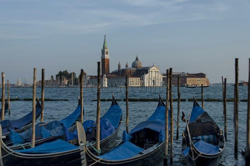 Le gondole hanno attraccato dal quadrato di St Mark e da San Giorgio Maggiore Island con la basilica Santa Maria della Salute nei immagine stock libera da diritti