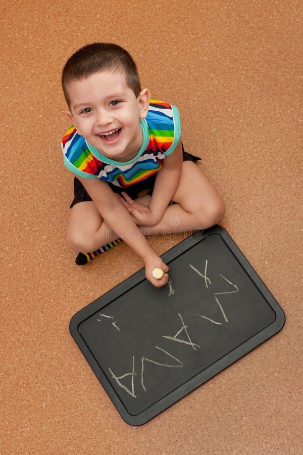 Le gosse heureux étudie l'écriture sur le tableau noir photographie stock