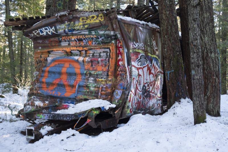 Le graffiti a couvert la voiture de train entourée par des arbres sur la hausse d'épave de train de Whistler photographie stock libre de droits