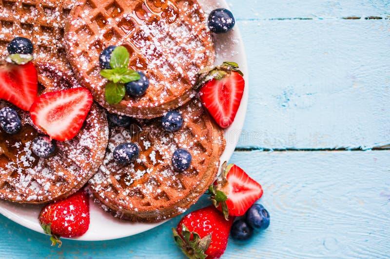 Le grain entier waffles avec des baies sur le fond en bois bleu photo stock