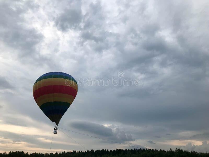 Le grand arc-en-ciel rond lumineux multicolore a coloré le ballon rayé rayé de vol avec un panier contre le ciel le soir image stock