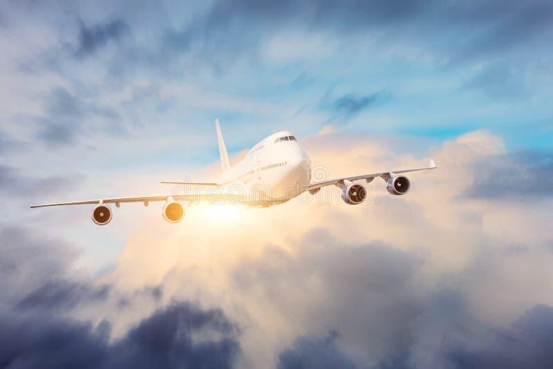Le grand avion de transport de passagers quatre moteurs de jet vole par les nuages denses avec le soleil lumineux photo stock