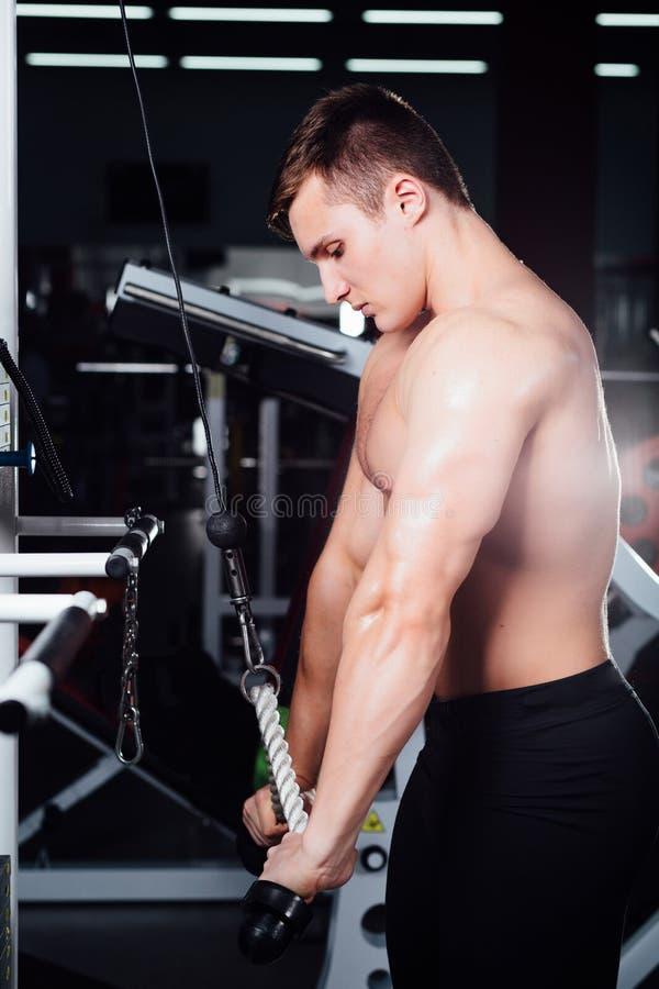 Le grand bodybuider fort sans chemises démontrent des exercices de croisement Les muscles pectoraux et la formation dure image stock