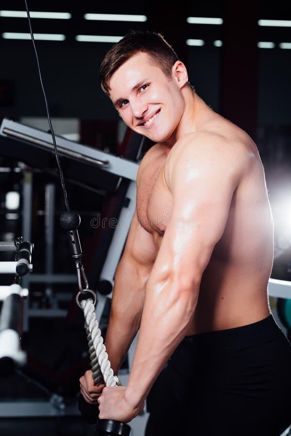 Le grand bodybuider fort sans chemises démontrent des exercices de croisement Les muscles pectoraux et la formation dure images libres de droits