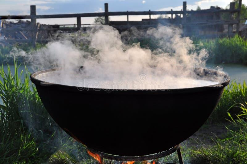 Le grand chaudron noir sur le feu avec la vapeur image stock