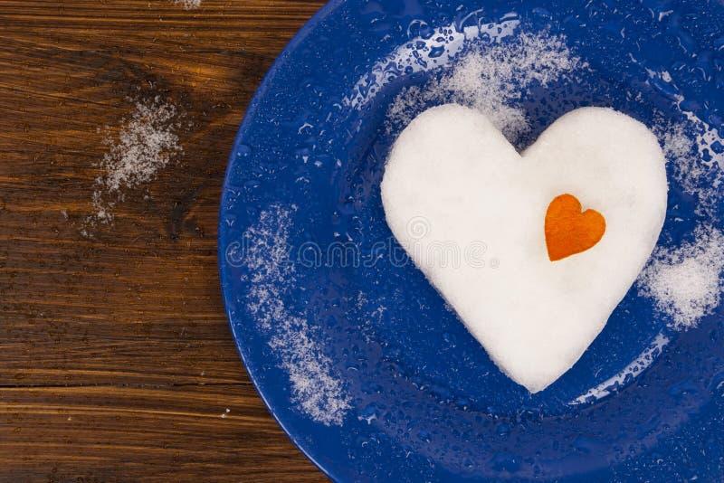 Le grand coeur de neige décoré du petit coeur orange se trouvant du plat bleu photographie stock libre de droits