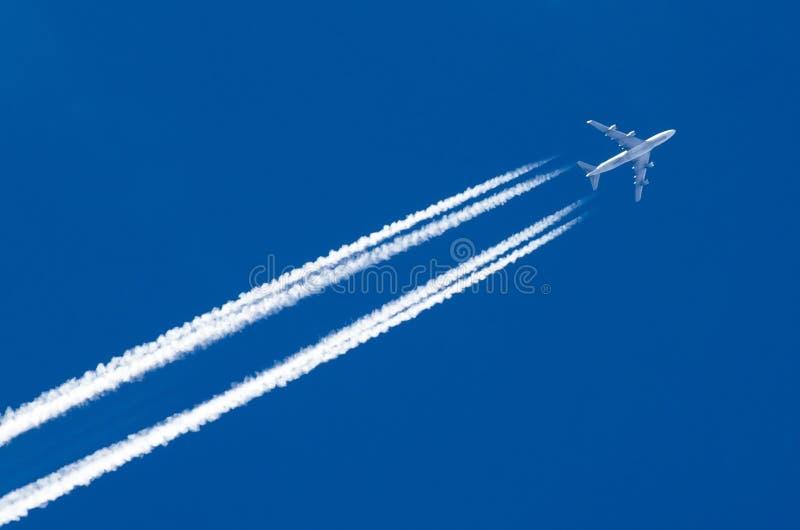 Le grand contrail d'aéroport d'aviation de deux moteurs d'avion opacifie photographie stock