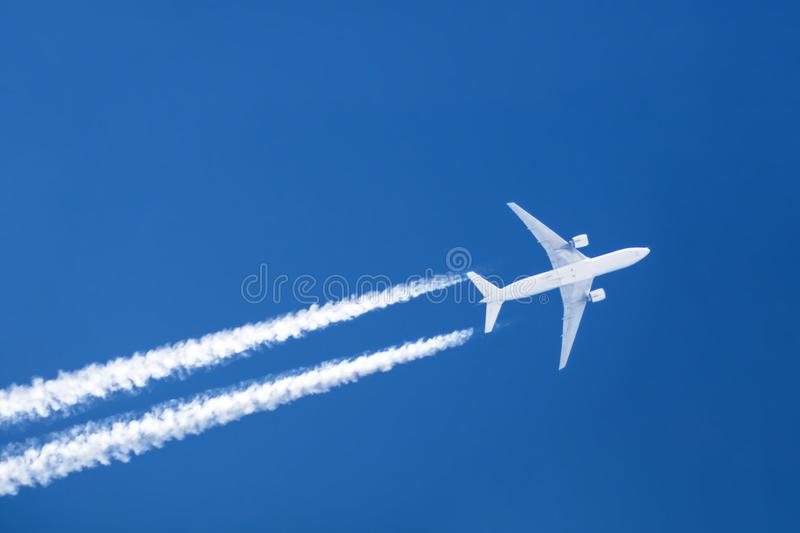 Le grand contrail d'aéroport d'aviation de deux moteurs d'avion opacifie photographie stock libre de droits