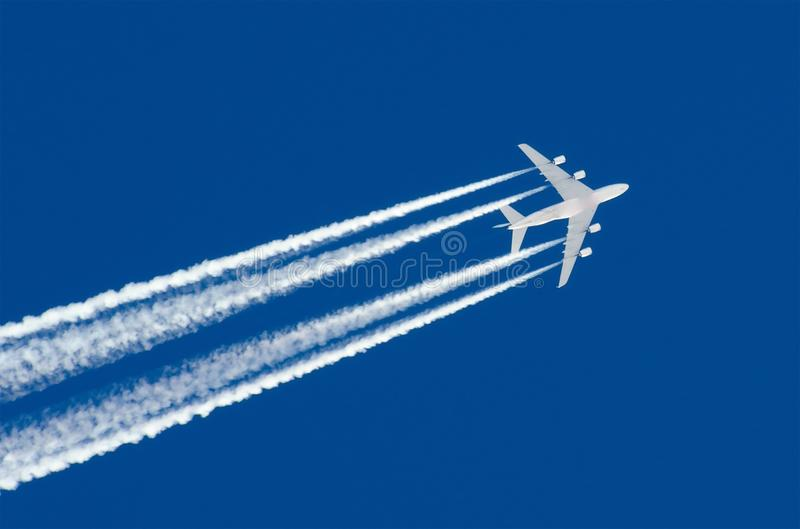 Le grand contrail d'aéroport d'aviation de quatre moteurs d'avion énorme opacifie photo stock