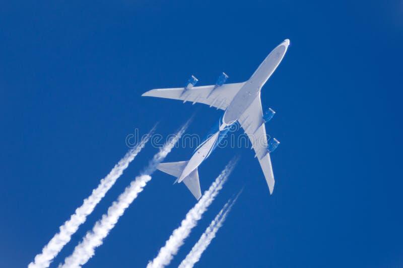 Le grand contrail d'aéroport d'aviation de quatre moteurs d'avion opacifie, extr photo libre de droits
