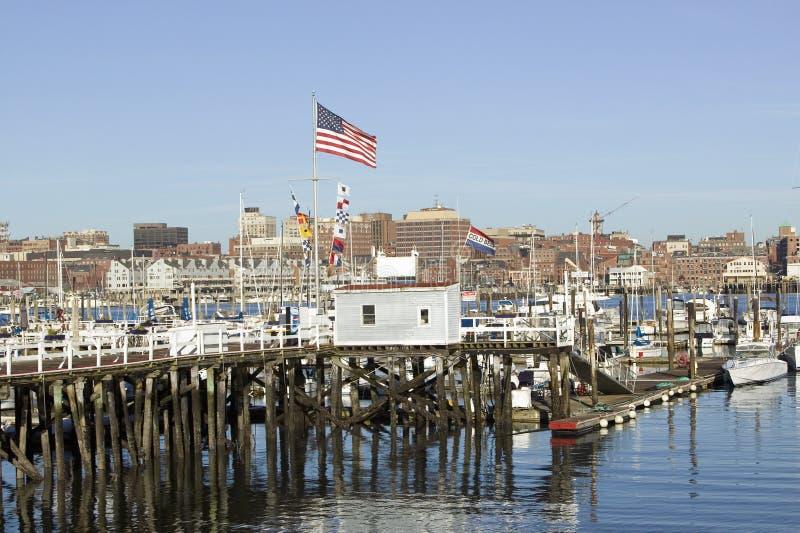 Le grand drapeau américain vole dans le port de Portland avec l'horizon du sud de Portland, Portland, Maine images libres de droits