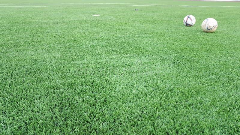 Le grand football artificiel vert de gazon avec des boules photographie stock