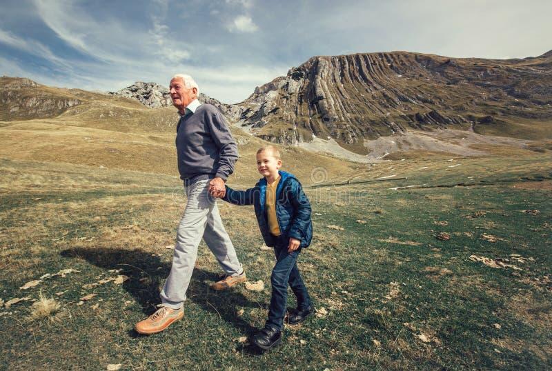 Le grand-père avec le petit-fils marche sur la route photographie stock libre de droits
