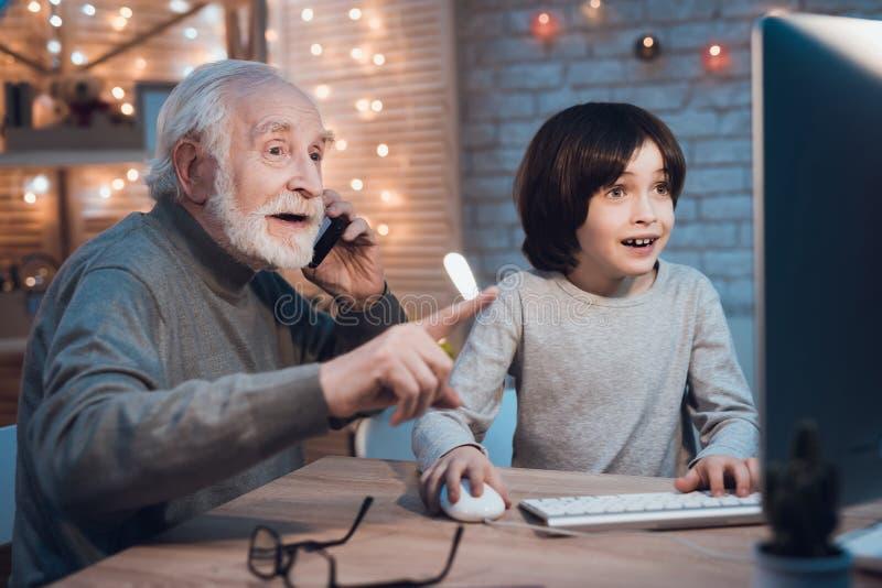 Le grand-père et le petit-fils jouent des jeux sur l'ordinateur la nuit à la maison Le grand-papa encourage pour le garçon photographie stock