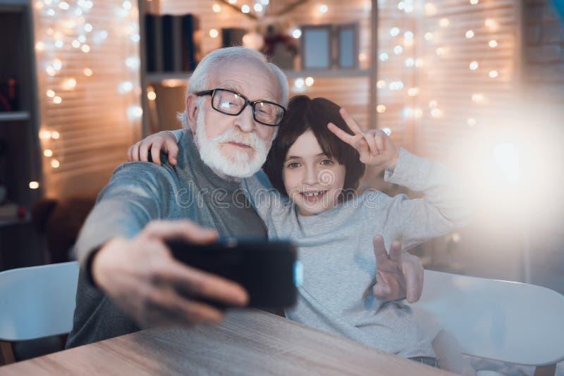 Le grand-père et le petit-fils prennent le selfie au téléphone la nuit à la maison photos stock