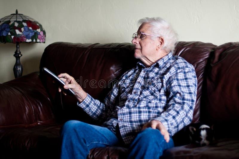 Le grand-papa change la chaîne de télévision avec à télécommande photographie stock