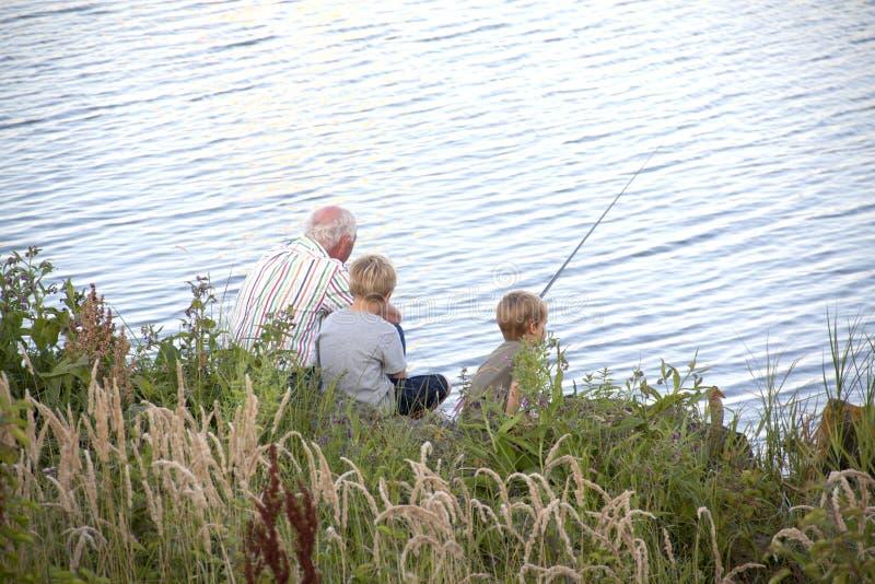 Le grand-papa enseigne à des petits-enfants la pêche image libre de droits