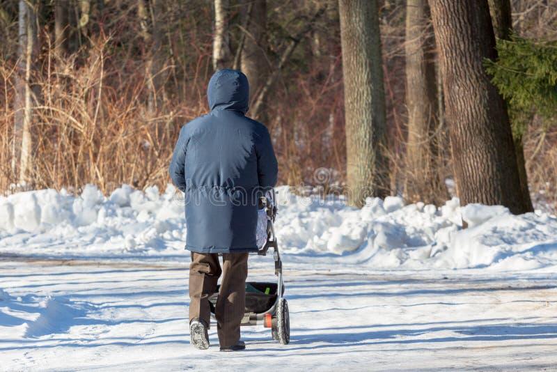 Le grand-papa marche avec un landau photos libres de droits