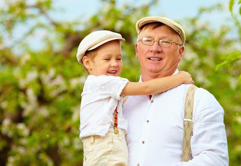 Le grand-papa mignon avec le petit-fils sur des mains font du jardinage au printemps photos libres de droits