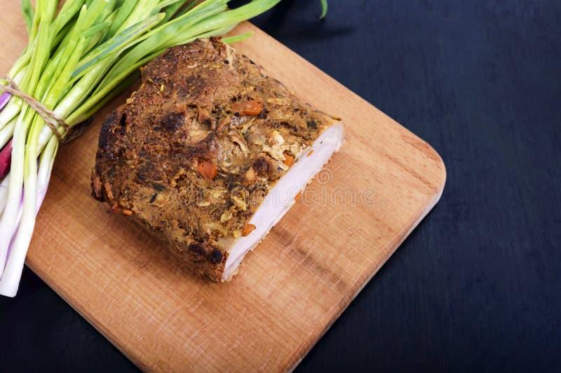 Le grand porc de morceau a fait le jambon cuire au four, aux oignons verts sur la planche à découper photo libre de droits