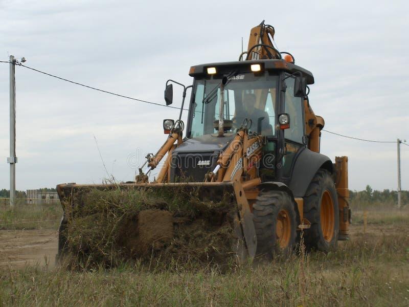 Le grand tracteur puissant enlève la terre travaille au chantier de construction images libres de droits