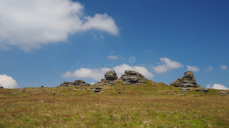 Le grande collegano il tor con le nuvole bianche in un cielo blu, Dartmoor immagine stock