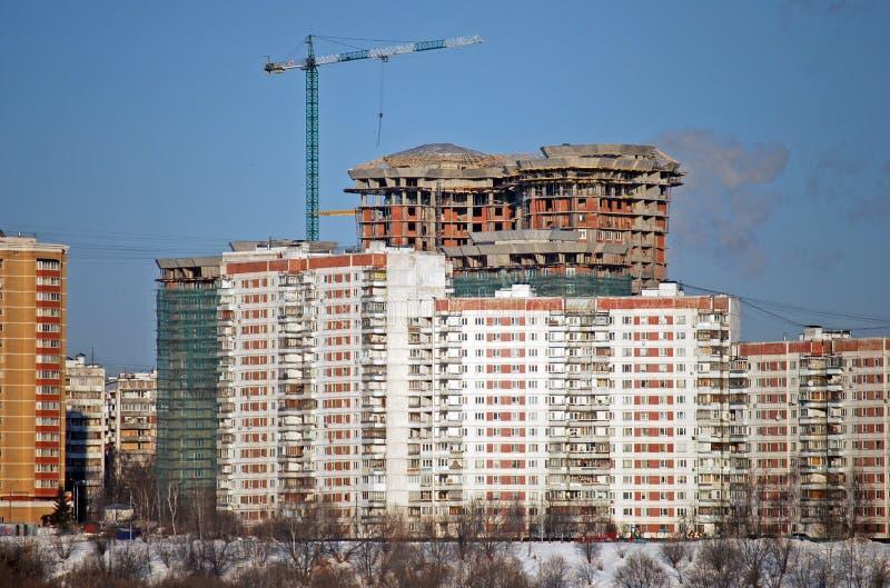 Le gratte-ciel habité avec la grue à tour dans la perspective du vieux bâtiment à plusiers étages est en construction photos libres de droits