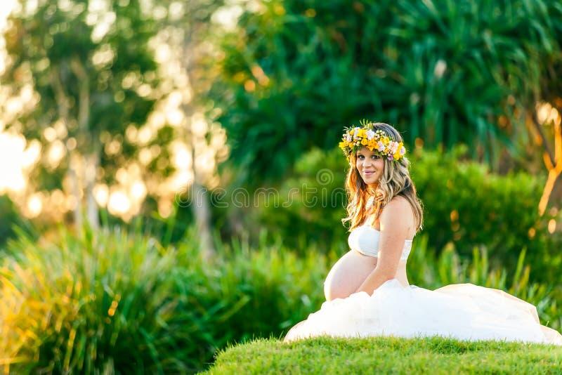 Le gravida kvinnan i den vita klänningen med blommor i hennes hår royaltyfria bilder