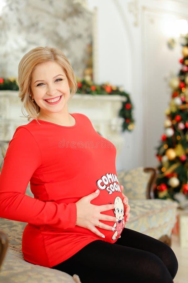 Le gravida kvinnan som bär den röda tröjan som bely kramar och sitter på soffan nära julgranen arkivbilder