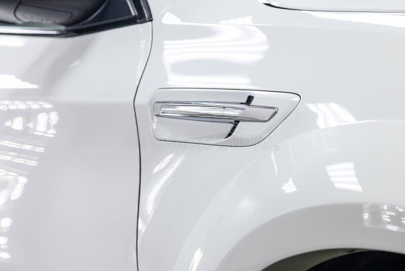 Le gril de ventilation d'amortisseur d'aile de partie antérieure avec la lumière de tour de la nouvelle voiture blanche chère mêm image libre de droits