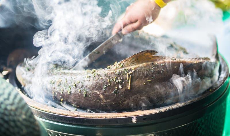 Le gril fumé de jardin de poissons et fument le processus du tabagisme photos stock