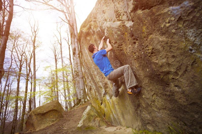 Le grimpeur bouldering sur les roches photo stock