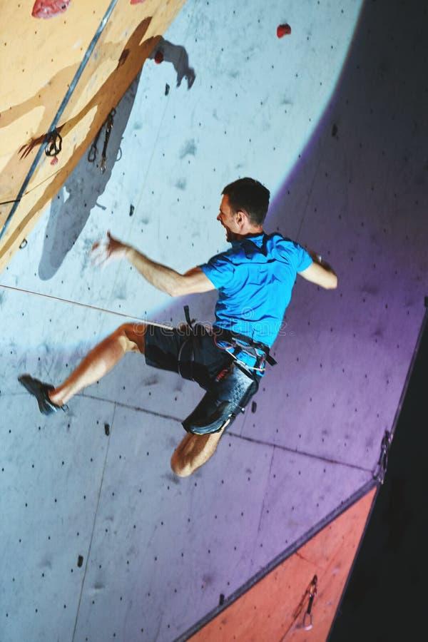 Le grimpeur d'homme monte a avec la corde sur le gymnase s'élevant et la chute image libre de droits