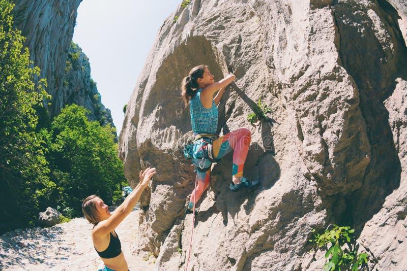 Le grimpeur de roche monte une roche photo stock
