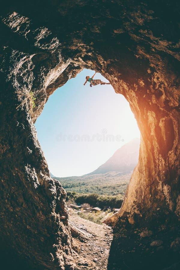 Le grimpeur de roche s'?l?ve dans la caverne photos stock