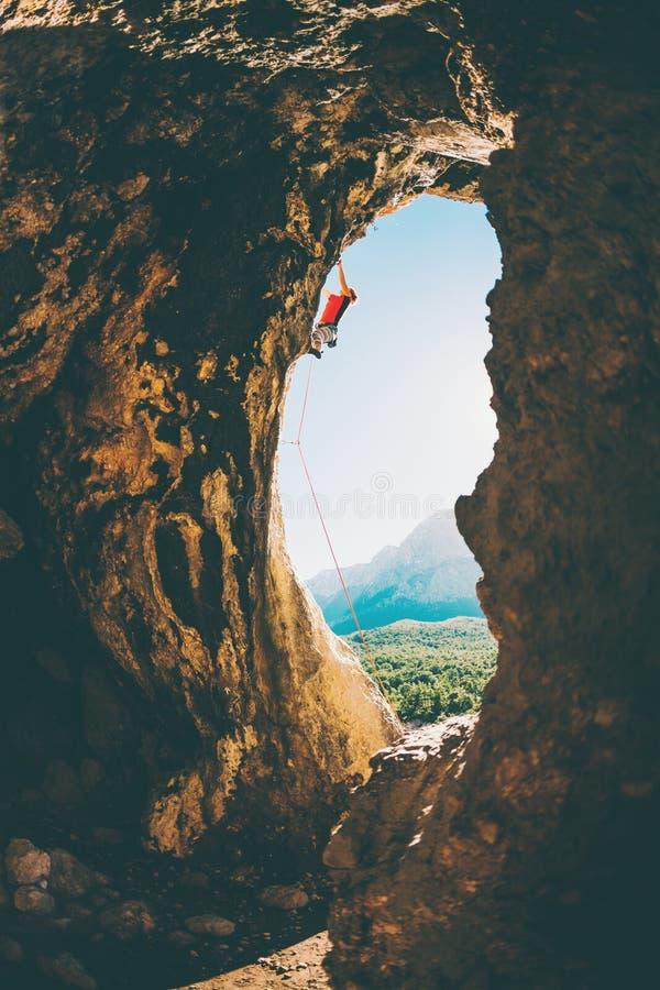 Le grimpeur de roche s'?l?ve dans la caverne images stock
