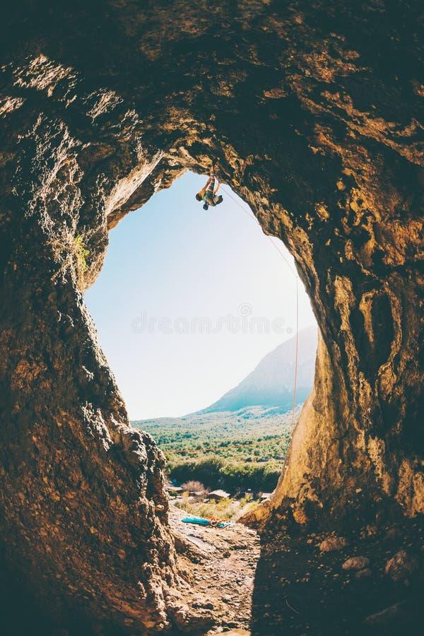 Le grimpeur de roche s'?l?ve dans la caverne image stock