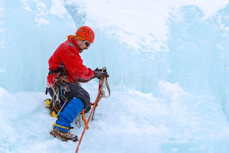 Le grimpeur dispose l'équipement pour escalader le mur de glace photographie stock