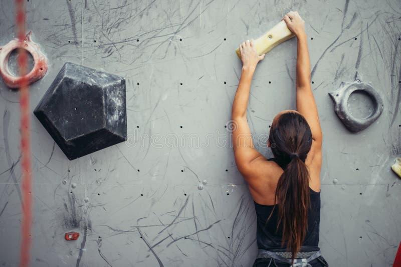 Le grimpeur remet tenir le rocher artificiel dans le gymnase s'élevant, tir de plan rapproché images stock
