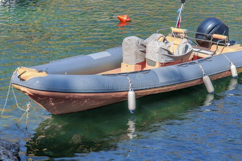 Le gris et le jaune ont accouplé le canot automobile en bois de vintage en mer photos libres de droits
