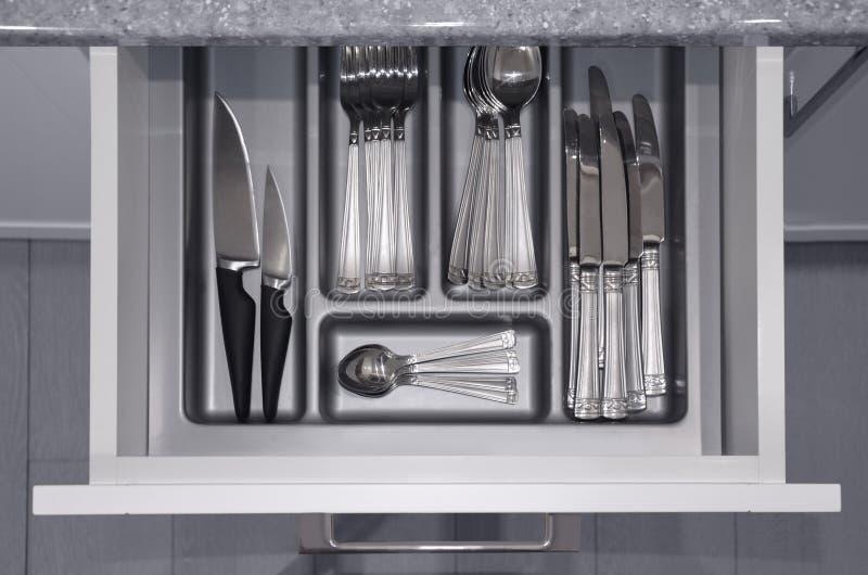 Le gris a ouvert le tiroir de cuisine avec un plateau et des couverts argentés réglés à l'intérieur Vue de ci-avant image image libre de droits