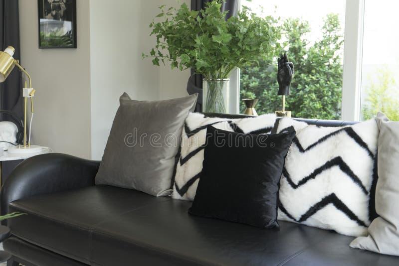 Le gris repose l'arrangement sur le divan beige dans le salon image stock