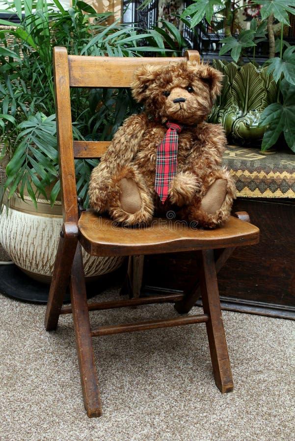Le Grizzle le nounours concernent une chaise de vintage photographie stock