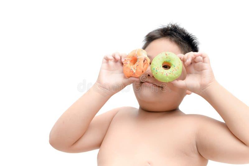 Le gros garçon obèse mange le beignet d'isolement images stock