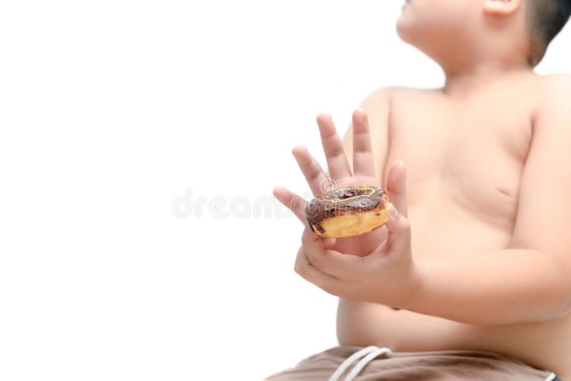Le gros garçon obèse refuse de manger le beignet d'isolement image stock