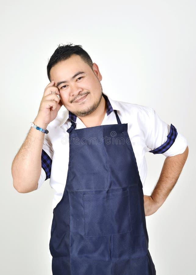 Le gros homme d'entrepreneur asiatique dans le tablier bleu profond font l'action comme pensant ayez une idée pour des affaires e image stock