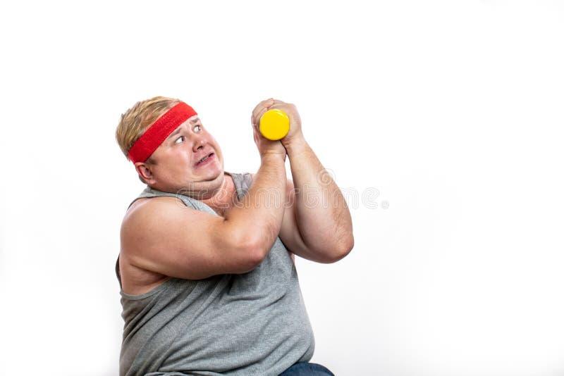 Le gros homme drôle dans le bandeau rouge montre ses muscles avec le dummbell et les émotions photographie stock