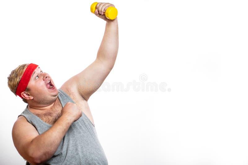 Le gros homme drôle dans le bandeau rouge montre ses muscles avec le dummbell et les émotions photographie stock libre de droits